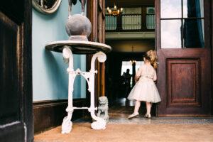 flowergirl looking through door at wedding