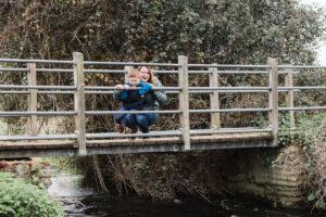 boy and mummy on bridge over a stream