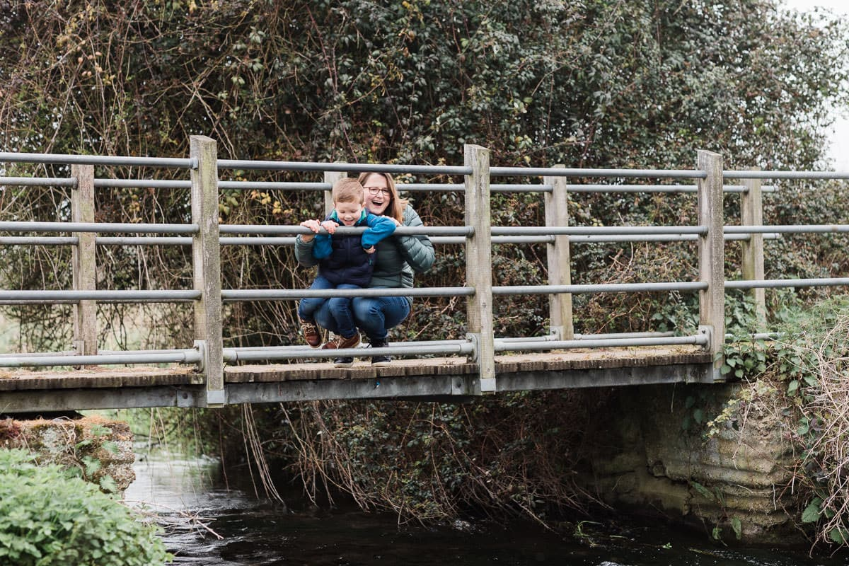 boy and mummy on bridge over a stream