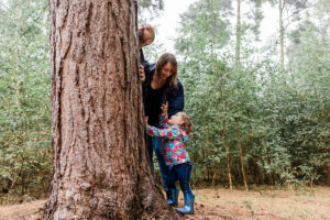 family looking up a tree in the woods