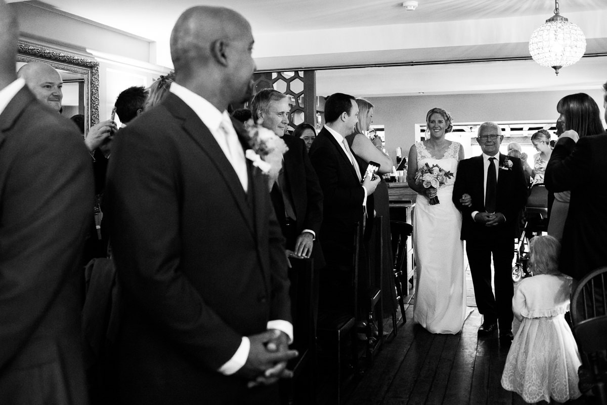 groom looks at bride walking down the aisle