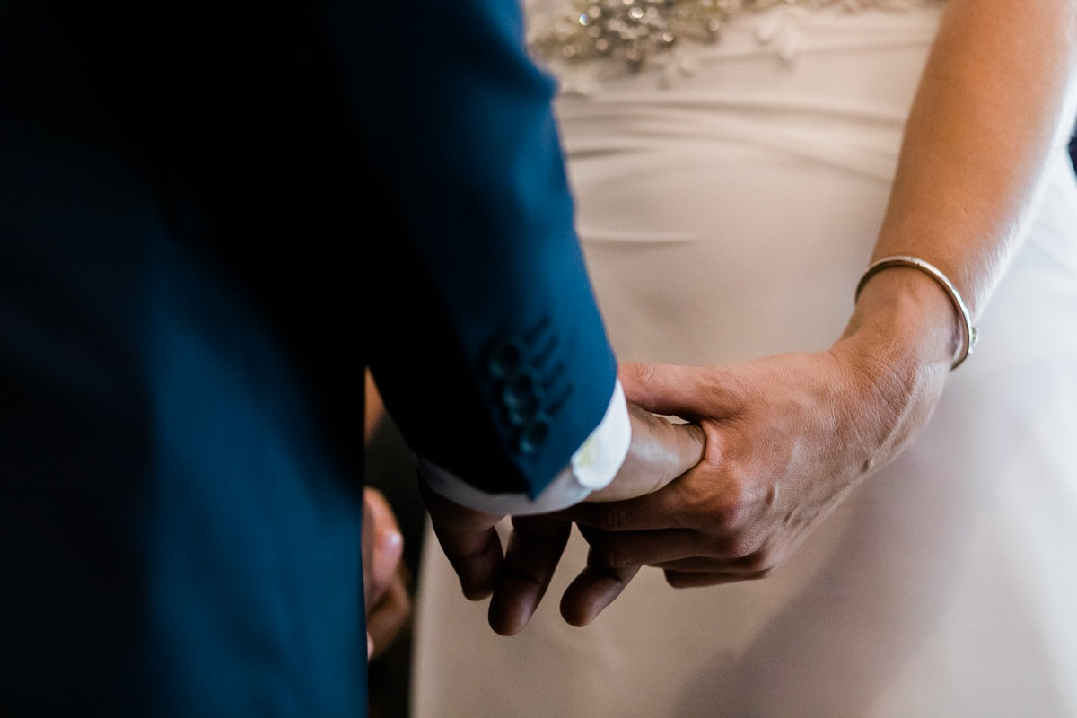 bride and groom holding hands as they get married