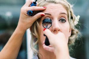 bride having eyelashes curled