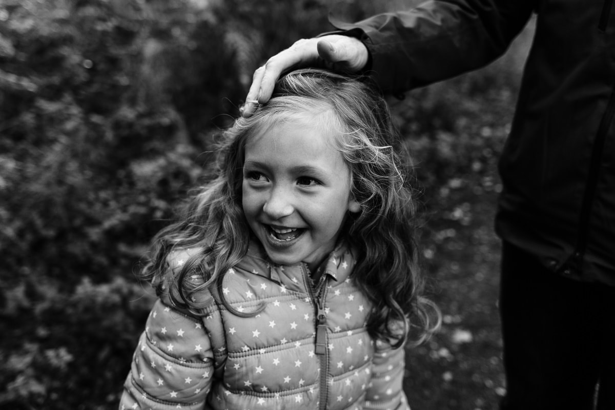 girl with dad's hand on her head
