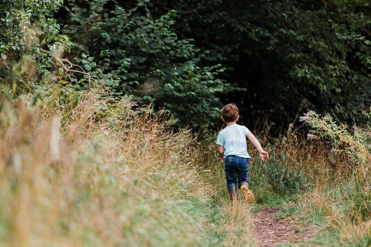 boy running into woods