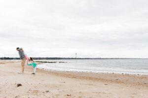 children with daddy on beach