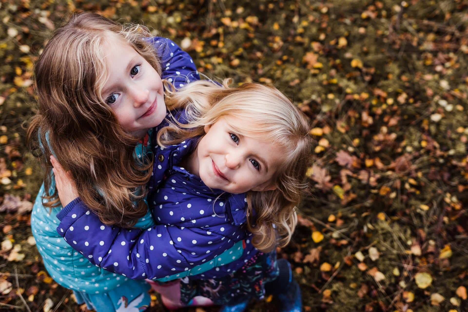 Sisters in autumn leaves