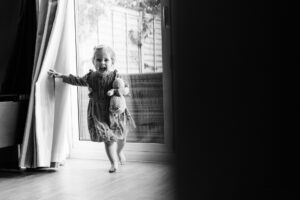 girl playing peepo with curtains