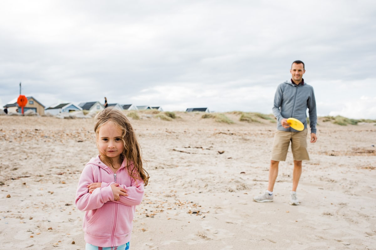 daddy and daughter play tickles on the beach