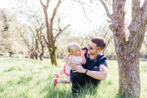 daddy and daughter cuddles in field