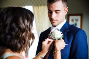 Groom's mother attaching buttonhole