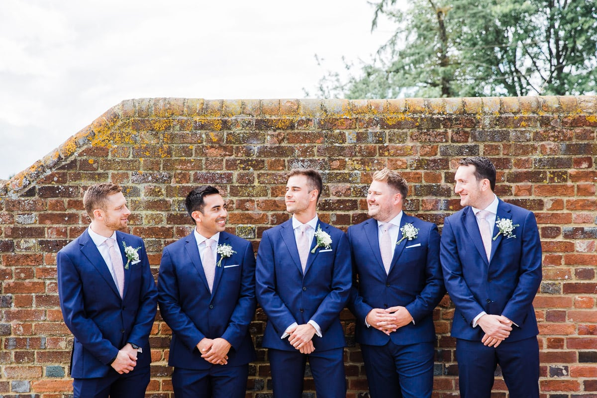 Groomsmen by garden wall at Lodge Farm Hitchin