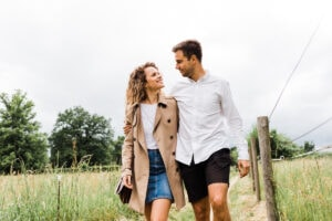 couple walking holding hands in a field