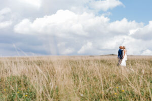 bride and groom kiss in field