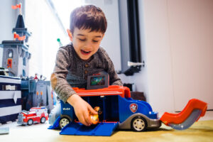 boy playing with red truck