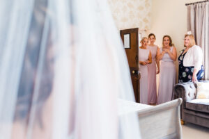 bridesmaids seeing bride in her dress