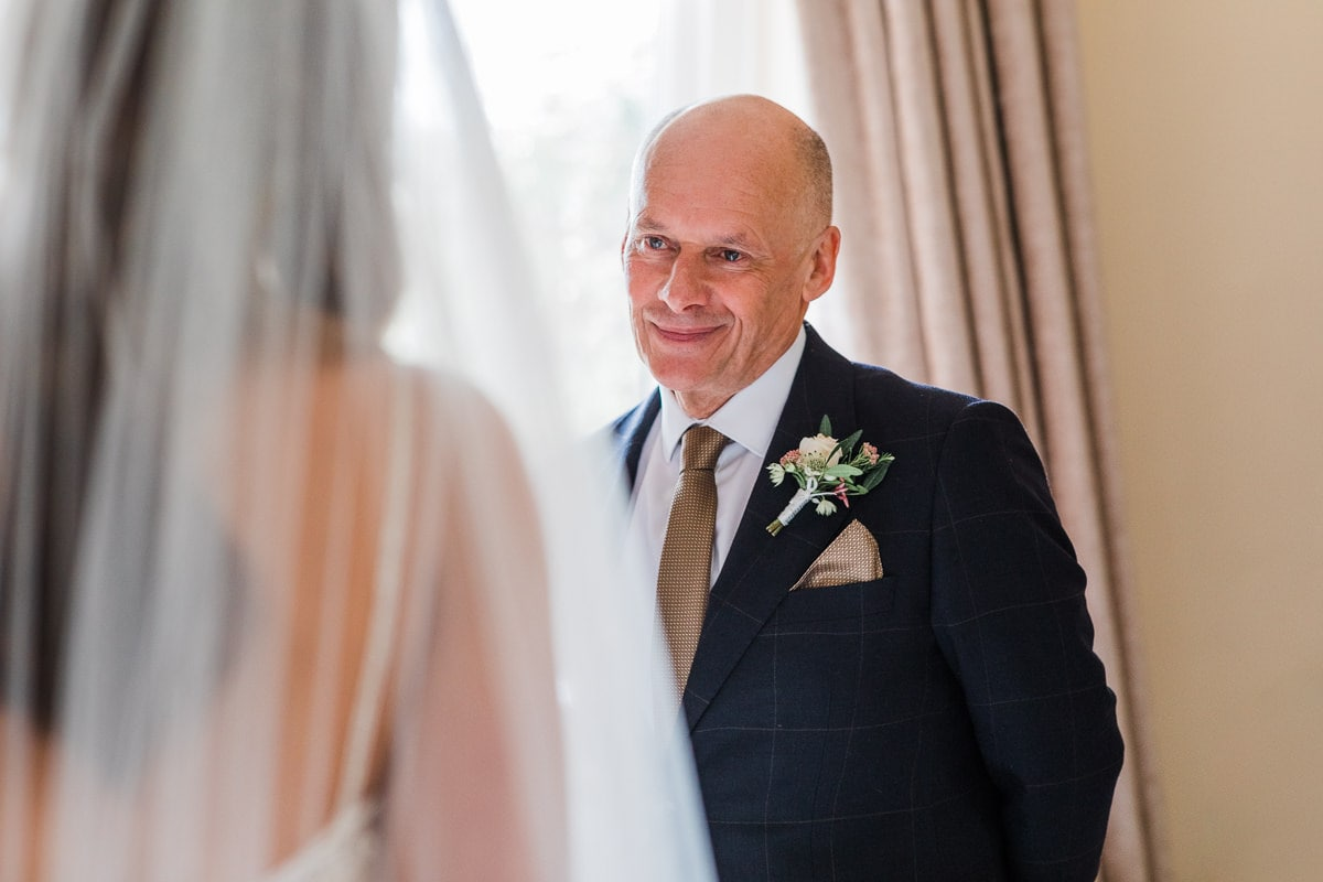 Father of the bride seeing daughter in her wedding dress