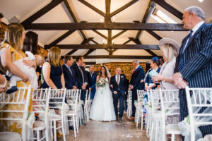 bride and father walk down the aisle at Hunters Hall
