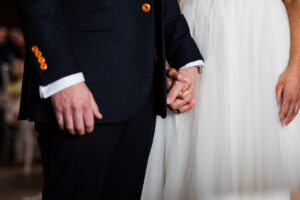 bride and groom hold hands during ceremony