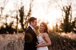 bride and groom in fields at sunset