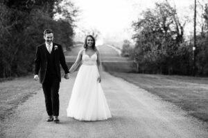 bride and grroom walking on Hunters Hall driveway