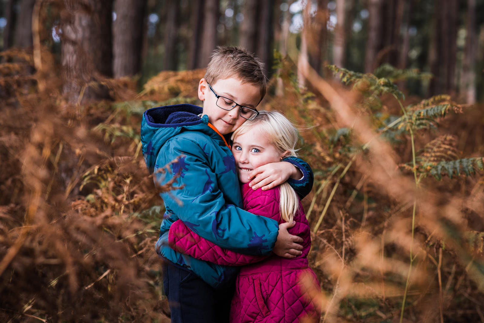 brother and sister cuddle in the woods