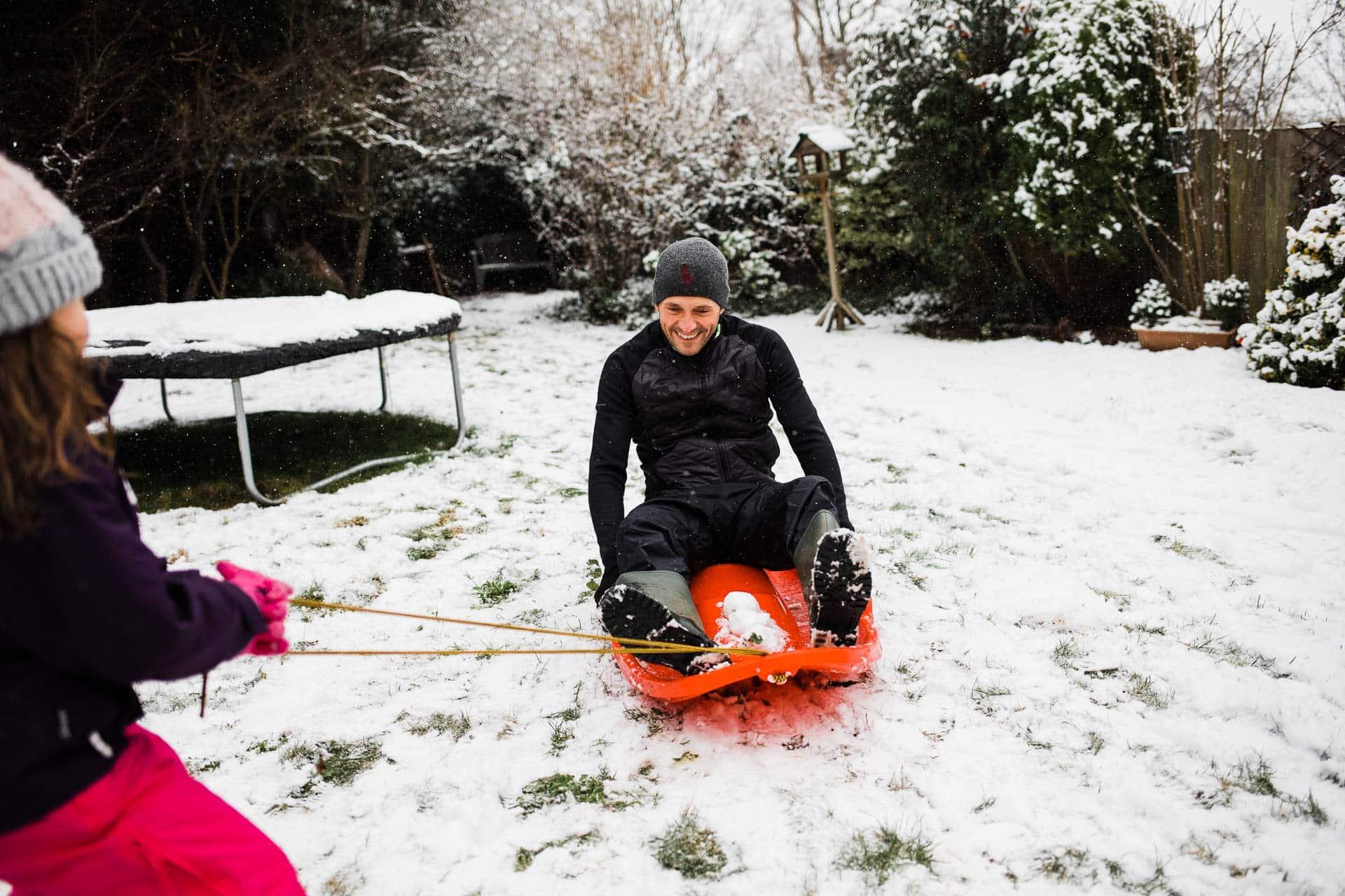 little girl pulls daddy on sledge