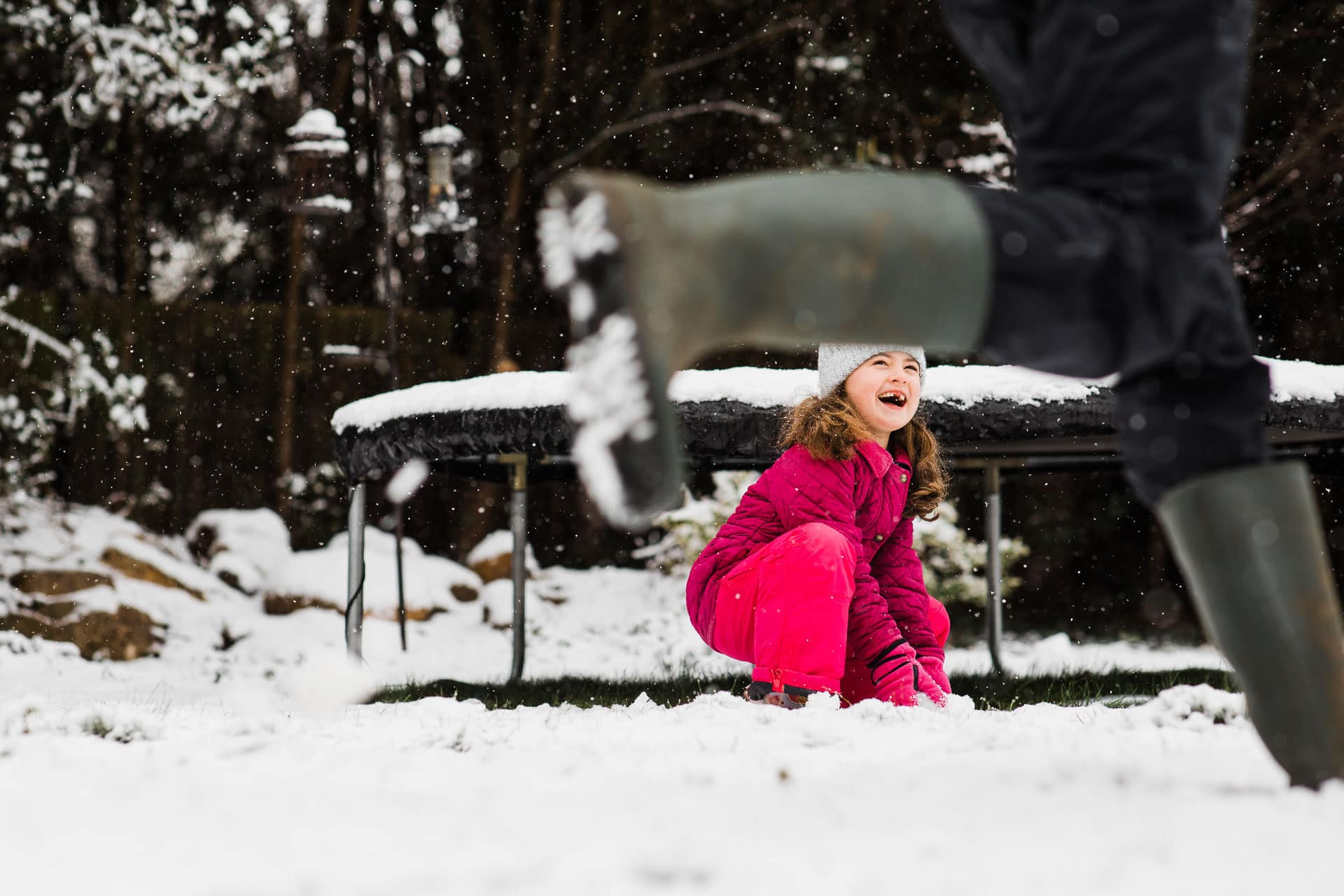girl in the snow and daddy running past in wellies